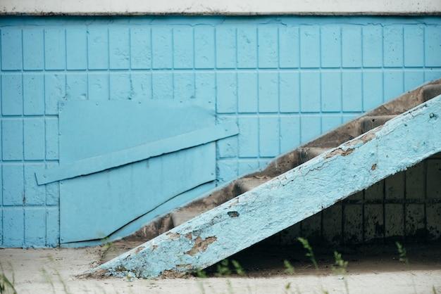 ハッチと階段のある建物の青い壁がクローズアップ Premium写真