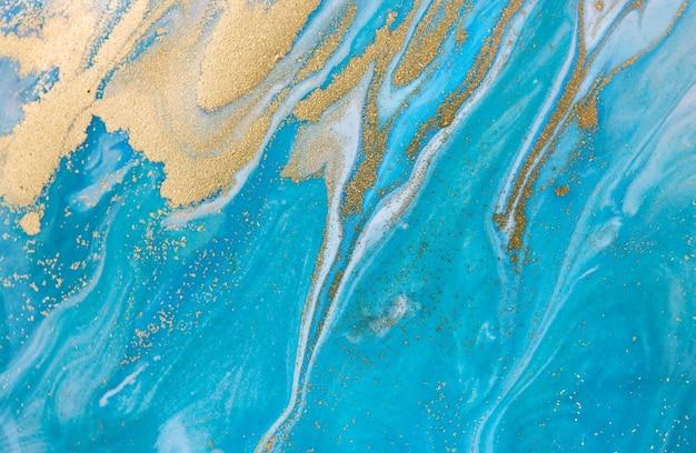 Синий волновой узор со слоями золотых блесток Premium Фотографии