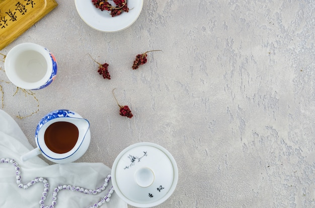 Blue and white chinese porcelain tea set with herbs on grey concrete backdrop Free Photo
