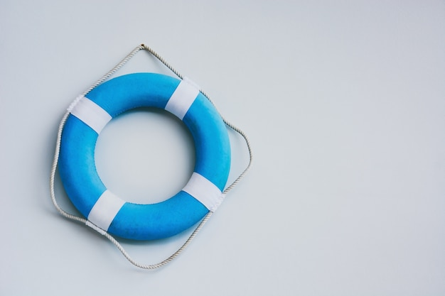 Blue and white safety torus or lifebuoy hanging on white wall background, copy space Premium Photo