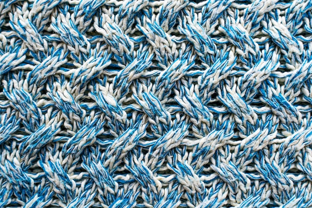 Blue and white texture of a knitted woolen fabric with a patterned weave. sweater background Premium Photo