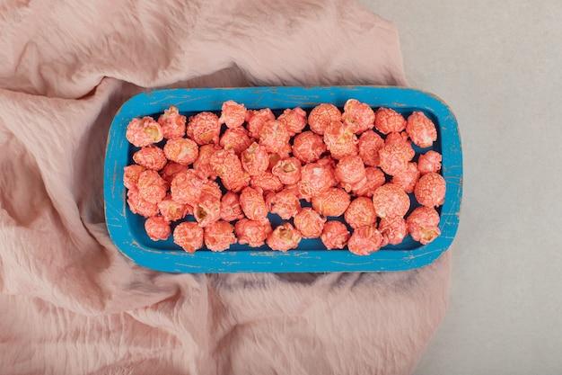 Vassoio di legno blu su una tovaglia, riempito di popcorn aromatizzato su marmo. Foto Gratuite
