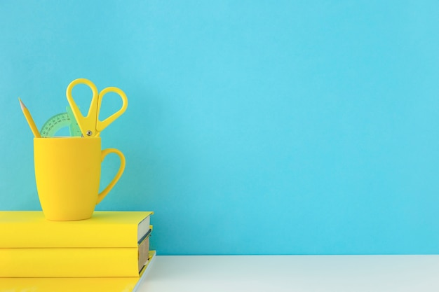 Blue workplace for students with yellow accessories Free Photo