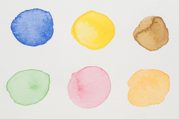 Blue, yellow, brown, green, pink and orange paints on white paper Free Photo