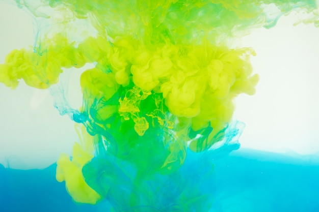 Blue and yellow paint mixing in water Free Photo