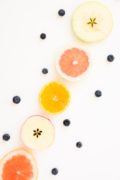 Blueberries decorated with slices of apple; orange and grapefruit isolated on white backdrop Free Photo