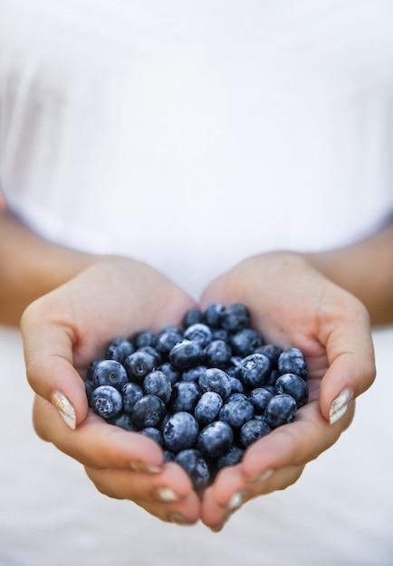 農家の手、女性の手にあるブルーベリー。果物、果実、食べ物、自然 Premium写真