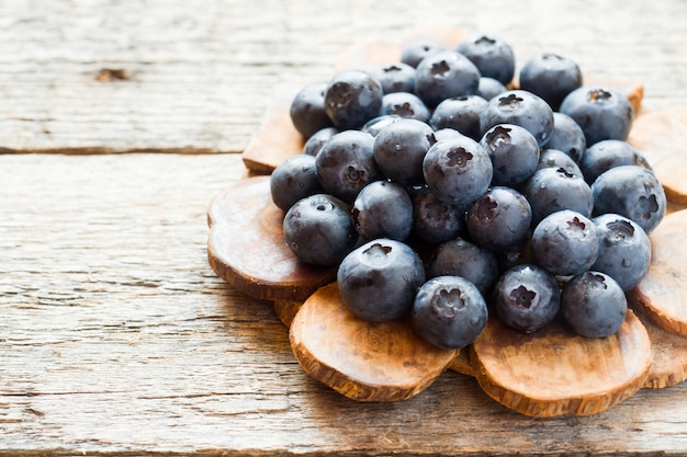 Blueberries on old wooden dishes, space for text Premium Photo