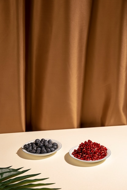 Blueberries and pomegranate seeds on plate with palm leaf over table against brown curtain Free Photo