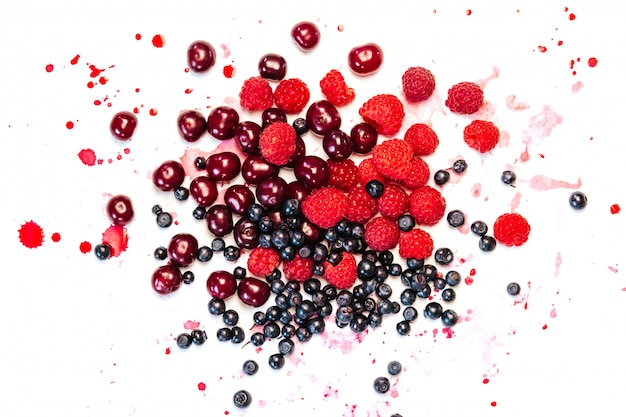 Blueberries, raspberries and cherries with drops of juice on white Premium Photo