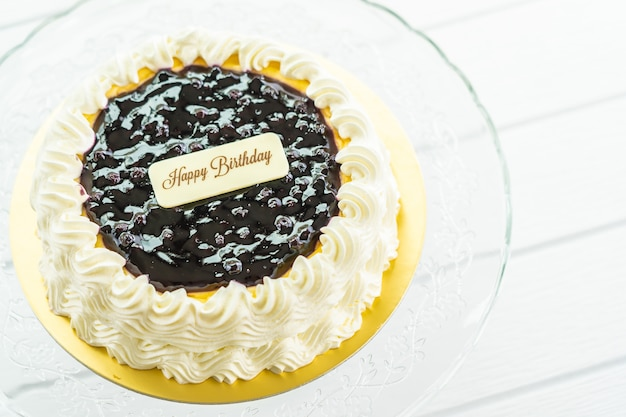 Blueberry cheese cake with happy birthday sign on top Free Photo