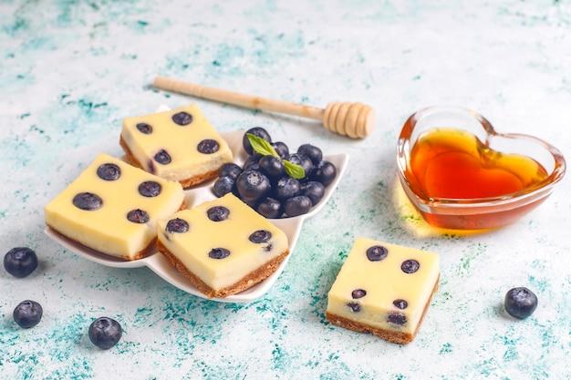 蜂蜜と新鮮なベリーのブルーベリーチーズケーキバー。 無料写真