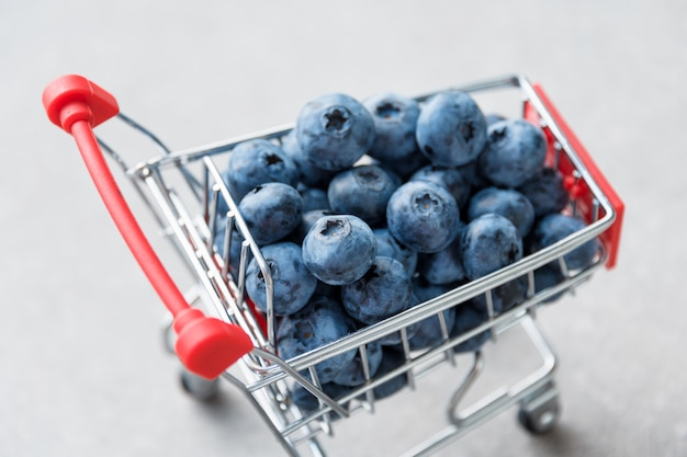 Blueberry fruits in mini shopping cart. selective focus on the blueberries in small trolley Premium Photo