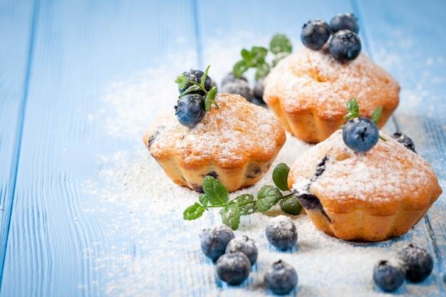 Blueberry muffin. homemade baked cupcake with blueberries, fresh berries, mint on wooden background. Premium Photo