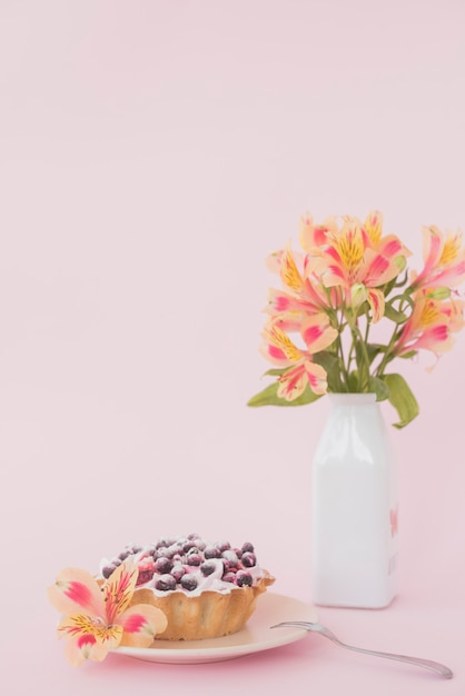 Blueberry tart with alstroemeria flower against pink background Free Photo