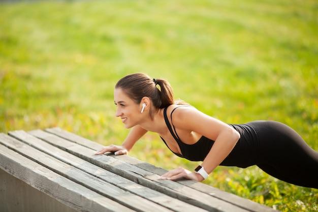スポーツウェアで腕立て伏せをし、緑豊かな公園でのトレーニング中にbluetoothイヤホンで音楽を聴くスポーティな美人20代の肖像画 Premium写真