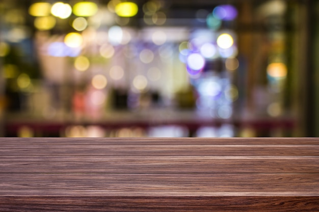 Blur cafe restaurant or coffee shop empty of dark wood table with light gold bokeh backgro Premium Photo