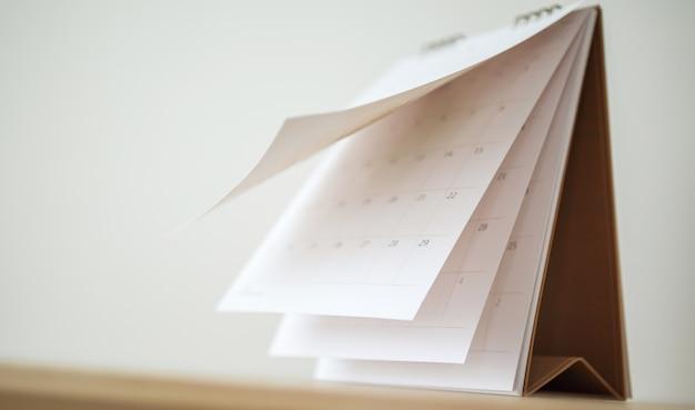 木製のテーブルの背景のビジネススケジュール計画予定会議のコンセプトにカレンダーページめくりシートをぼかす Premium写真