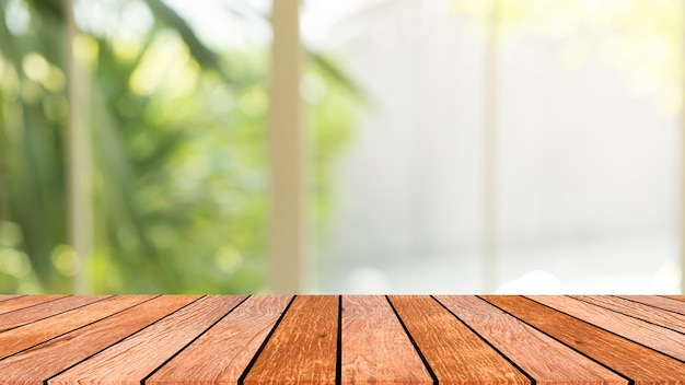 Blur garden view from window with morning light with wood table perspective for background Premium Photo