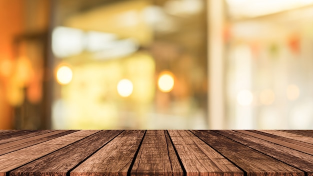Blur restaurant cafe light color with vintage brown wood tabletop background Premium Photo