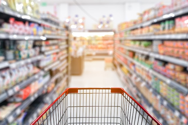 Blur supermarket aisle with empty red shopping cart Premium Photo