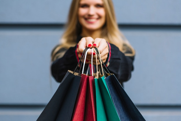 Blur young woman showing colorful shopping bags Free Photo