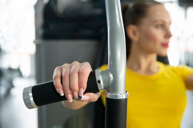 Blured портрет молодой кавказской женщины разрабатывая на тренажере внутри спортзала Premium Фотографии