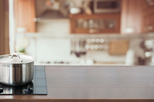 Blurred and abstract kitchen background. wooden tabletop with pan and defocused modern kitchen. Premium Photo