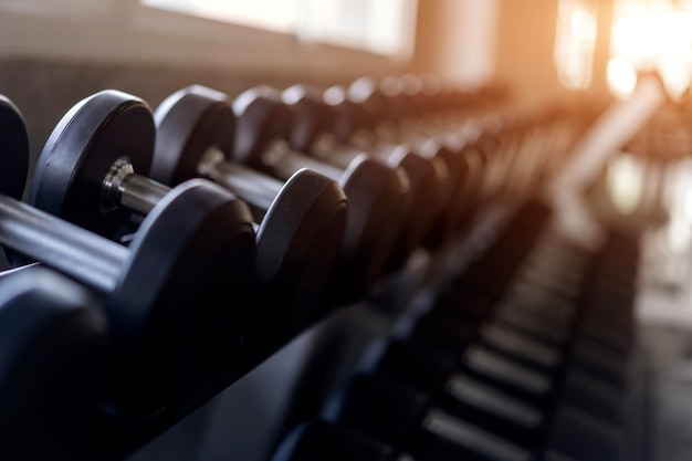 Blurred background of rows of black dumbbells on rack in the gym Premium Photo