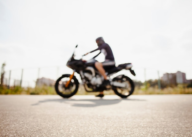 Blurred biker parked on the road Free Photo