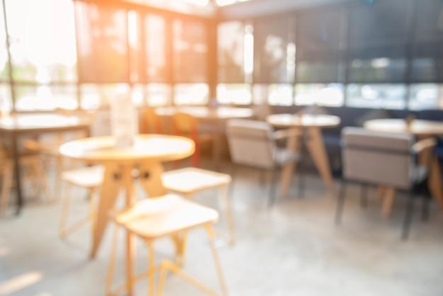 Затуманенное кафе кафе с солнечным светом. аннотация современного дизайна стола в ресторане. Premium Фотографии