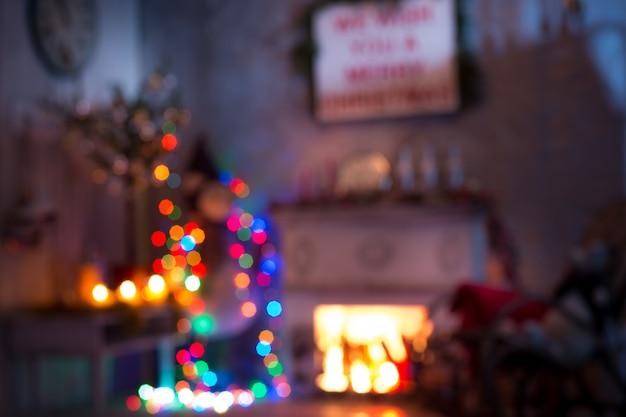 Gli interni sfocati di natale e capodanno del salotto. vecchia sedia a dondolo all'albero decorato e spazio camino. Foto Gratuite