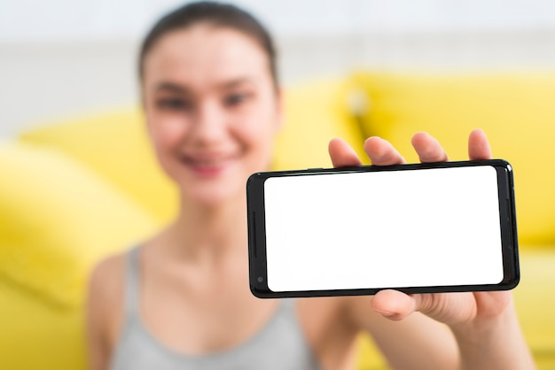 Blurred fitness girl showing mobile phone Free Photo