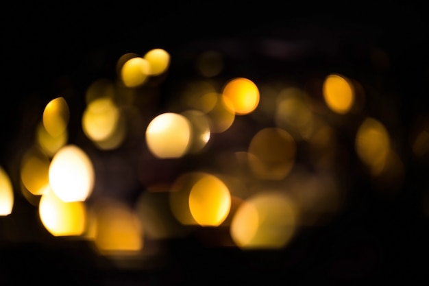 Blurred gold bokeh on black background. glowing yellow lights bokeh in the dark, reflections Premium Photo
