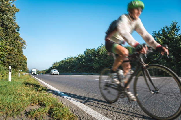 Blurred image of cyclists athletes racing at high speed on the highway Premium Photo