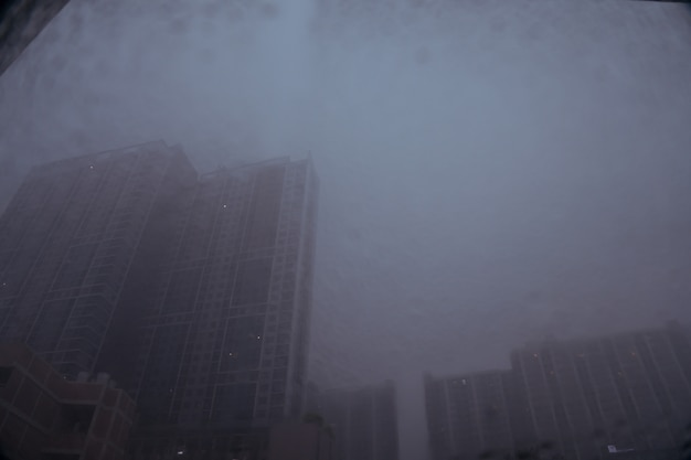 Blurred image of drops of rain on mirror with buildings and road background Premium Photo
