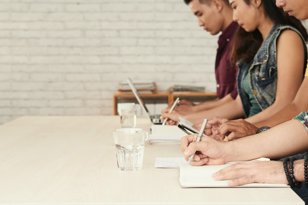 Blurred image of row of students busy writing test in classroom Free Photo