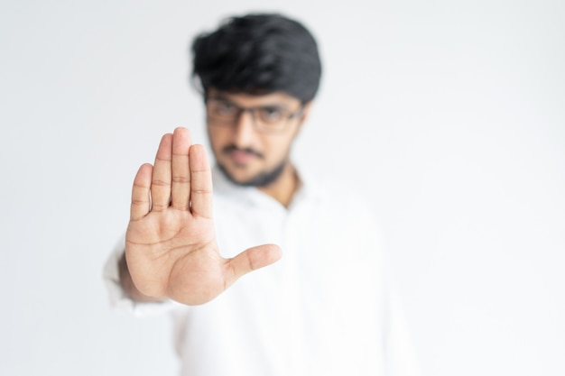 Blurred indian man showing open palm or stop gesture Free Photo