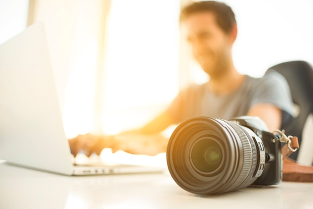 Blurred man using laptop behind dslr camera on desk Premium Photo