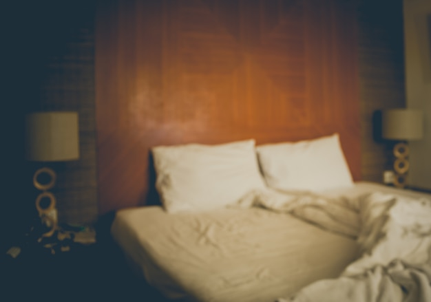 An blurred messy bed with white linens in vintage tone. Free Photo
