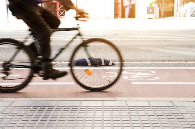 Blurred motion of cyclist riding on cycle lane near the sidewalk Free Photo
