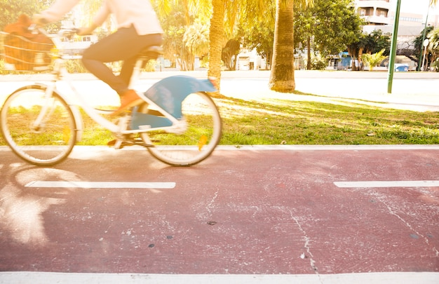 Blurred motion of a person riding the bicycle in park Free Photo