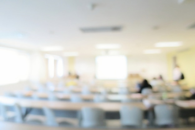 長いテーブル、椅子、プロジェクター、大きな窓がある講義室または会議室がぼやけている。教育。 Premium写真