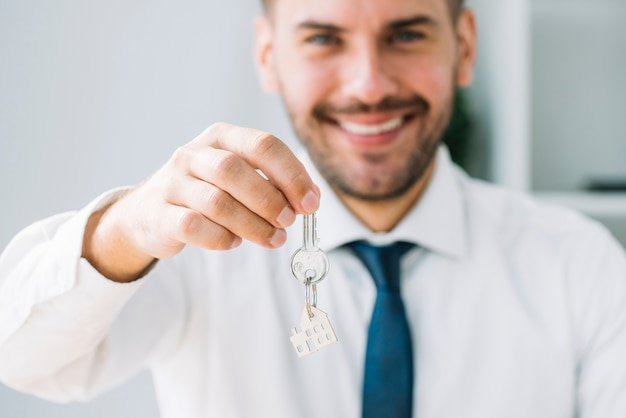 Blurred real estate agent holding key Free Photo