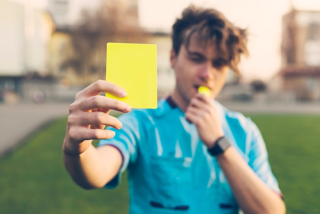 Blurred referee showing yellow card Free Photo