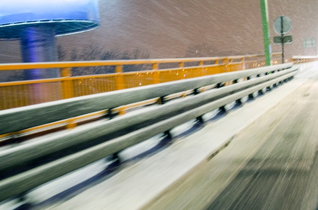 Blurred safety travel barrier construction in viaduct covered with snow Premium Photo