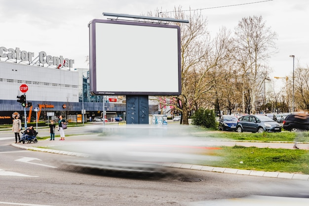 Blurred vehicle passing by the blank billboard on the road Free Photo