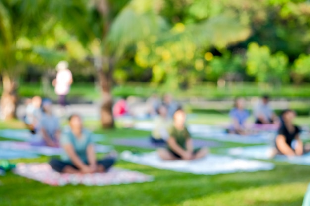 Blurred view a group of thai people was practice yoga exercise on public parks Premium Photo