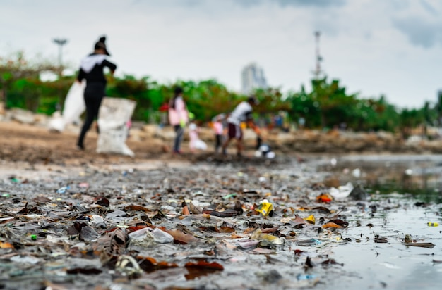 Blurred of volunteers collecting garbage. beach environment pollution. Premium Photo