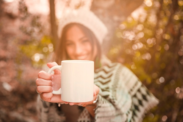 Blurred woman demonstrating mug in forest Free Photo